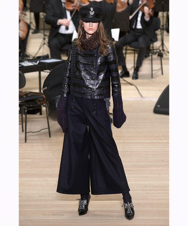 The nautical setting enveloped the collection. Lagerfeld re-appropriated the wardrobes of merchant navy crews in the spirit of Gabrielle Chanel – who famously reimagined the striped sailor top and pea coat from men.