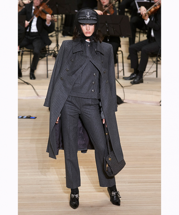 "Lagerfeld described mood and look of the show as ""sailors who haven't taken to the water."" Pieces were accented with sailor collars, jackets that are more or less fitted, long redingotes, mini-skirts and extra-wide trousers designed to feminise."