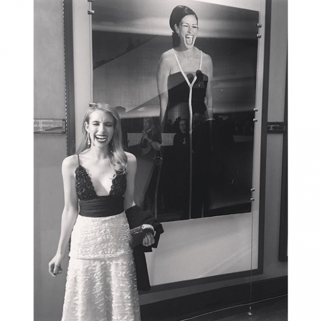 Emma Stone in front of a photo of her Aunt's famous Oscar-winning moment