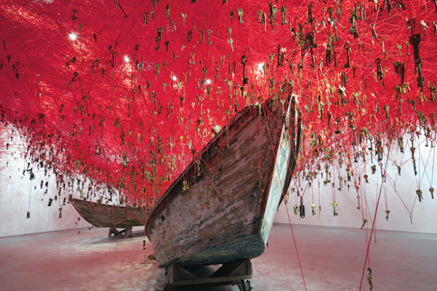 "Japan: Chiharu Shiota, The Key in the Hand<p><span style=""font-size: 17px; line-height: 29px;"">The installation of Japanese-born, Berlin-based artist Chiharu Shiota has fast become a crowd favourite and a contender for the most instagrammed artwork from the Biennale, and it's easy to see why. Her work is irresistibly beautiful in photos, let alone in the flesh. Walking into the Japanese pavilion feels like you have been swept into the set of a midsummer night's dream, draped in a forest of delicate crimson overgrowth. Shiota's work is a meditation on memory, featuring two wooden boats beneath a canopy of thread, cascading with thousands of keys from all over the world. In our daily lives, keys protect valuable things like our houses, assets, and personal safety, and in the process accumulate countless multilayered memories that dwell within us. The boats symbolise two hands navigating through a sea of memories and accumulating individual memories. Continuing the theme of memory Shiota also presents four heart-warming video installations of small children recounting memories from before and immediately after they were born. Among so much gloom and doom at this year's Biennale, Shiota's work is pure unadulterated joy which lingers in your memory, much like the keys trapped in yarn.&nbsp;</span></p>"