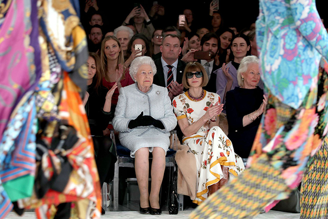 The Queen sat front row in a royal first at Richard Quinn before presenting the designer with the first ever Queen Elizabeth II British Design Award. Her FRow buddy? Who else but the queen of fashion, Vogue US Editor-in-Chief, Anna Wintour.