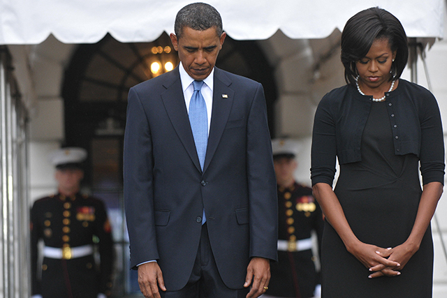 Barack and Michelle Obama observe a moment of silence to mark the eighth anniversary of the 9/11 attacks September 11, 2009 on the South Lawn of the White House in Washington, DC