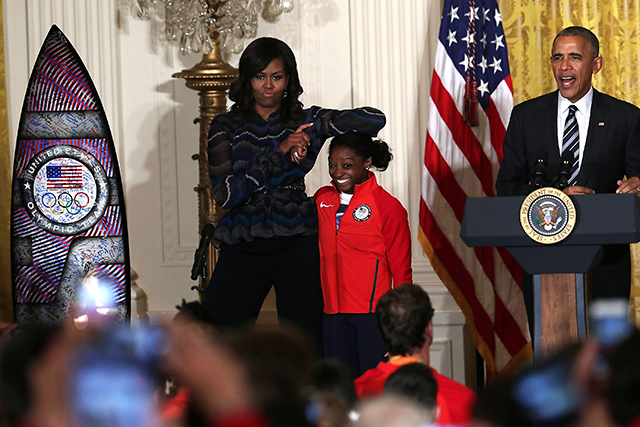 Michelle Obama rests her elbow on the head of Olympian Simone Biles as they welcome the 2016 US Olympic and Paralympic teams to the White House to honor their participation and success in the Rio Olympic Games