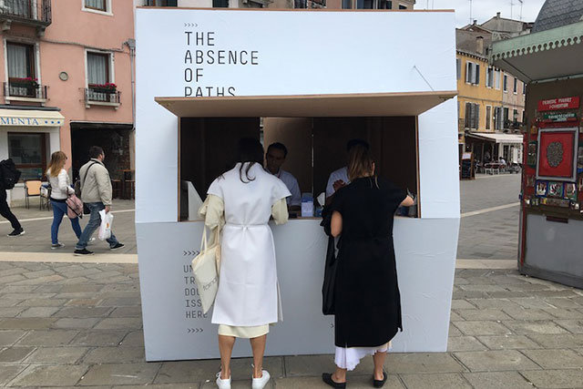 "TUNISIA, 'The Absence of Path': Comprising three separate issuing locations scattered across Venice, The Absence of Paths is an interactive performance that raises questions surrounding human migration, national identity and the concept of a state. Each kiosk is manned by Tunisian refugees who issue imitation visas referred to as freesas – a document which aims to ""endorse a philosophy of universal freedom of movement without the need for arbitrary state-based sanction."""