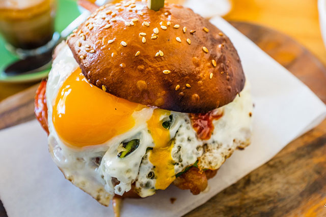 Kepos Street Kitchen Redfern, $14: This delightful b&e comes on a crunchy, toasted brioche roll, and lightly fried egg, extra crispy bacon, chilli jam, spinach and lovely roasted tomatoes which all simultaneously melts in the mouth.