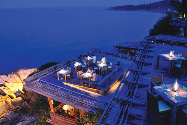 Dining On The Rocks, Koh Samui, Thailand. Suspended above the rocks overlooking the tranquil tropical waters of the Gulf of Thailand, this alfresco diner shows blazing talent in both food and views. Shades essential.